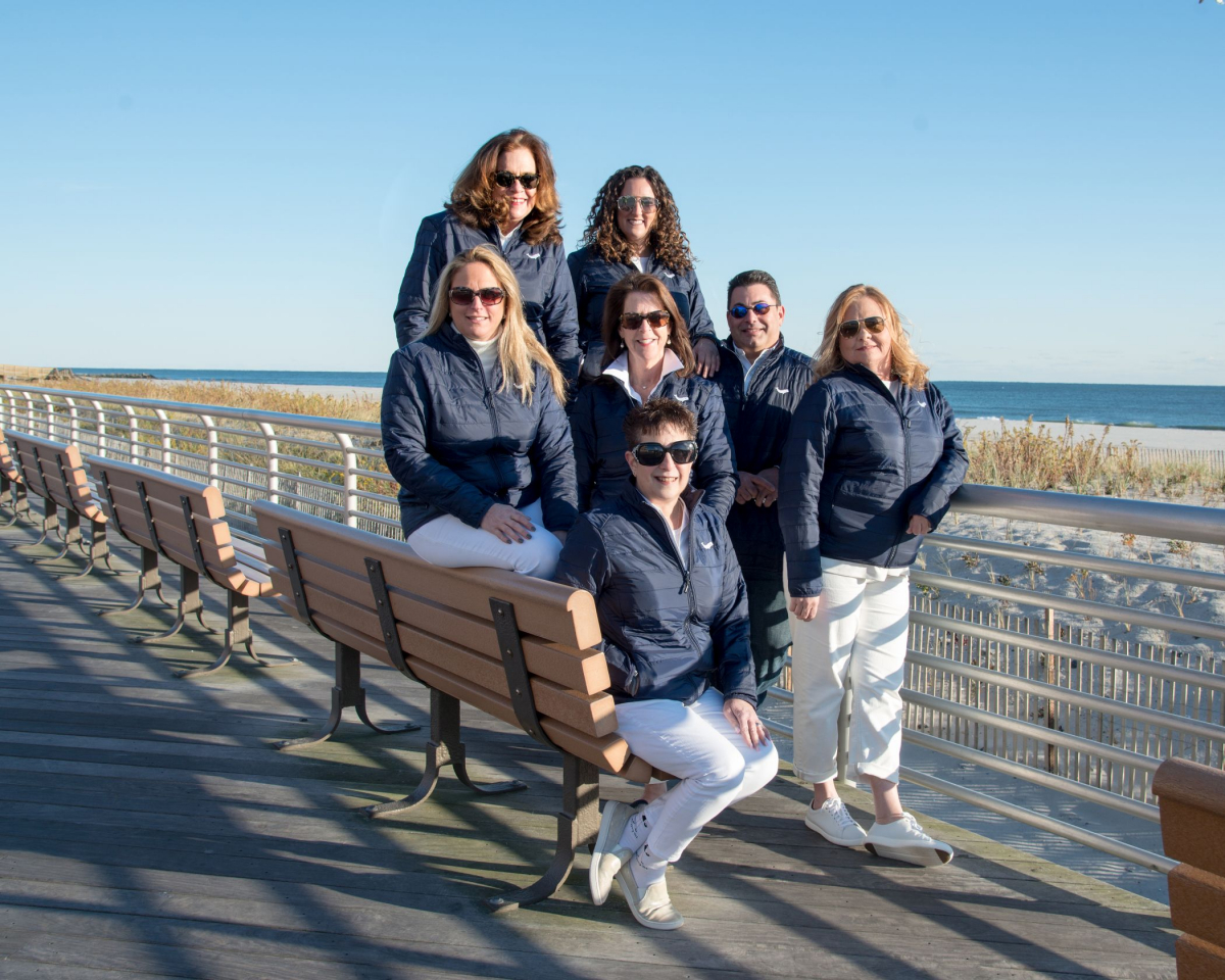 Daniel Gale Sotheby's International Realty's South Shore Coastal Division team loves the beach in every season.  Pictured here, (l-r) back row: Gloria Romanowski, Kelly Forman; middle row: Rosemary Talkin, Adrian Boland, Dan Amir, Ann Turner; seated in front: Robyn Goldowski.