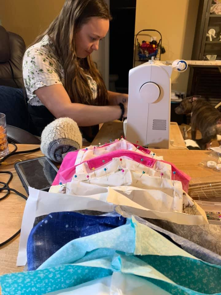 Felicia Bailey at her sewing machine making masks.